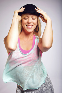 Woman looking happy while dancing in studio. Studio shot on grey background.