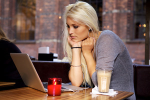 Woman looking on her laptop on a cafe.