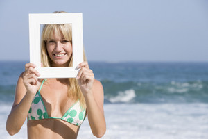 Woman looking through empty frame on beach