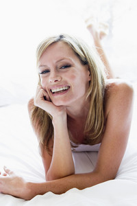 Woman lying in bed laughing