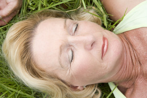Woman lying in grass sleeping