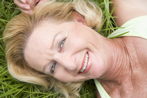Woman lying in grass smiling