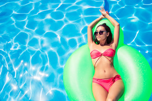 Woman lying on air mattress in swimming pool
