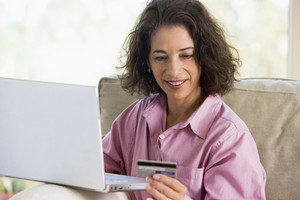 Woman making online purchase at home sitting on sofa
