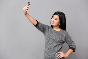 Woman making selfie photo on smartphone