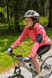 Woman mountain biking in forest motion blur training race