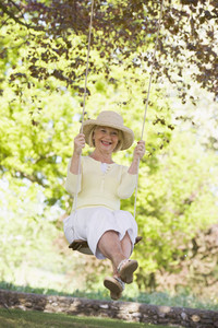 Woman on a swing outdoors smiling