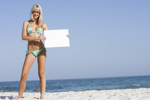Woman on beach holding blank card wearing bikini