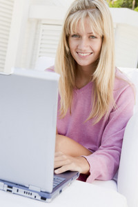 Woman on patio using laptop smiling