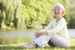 Woman outdoors at park by lake smiling