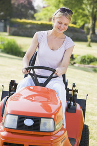 Woman outdoors driving lawnmower smiling