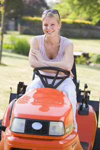 Woman outdoors with lawnmower smiling