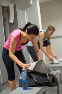 Woman packing bag at gym's locker room with friend in background