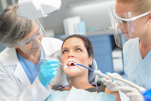 Woman patient dental check open mouth professional dentist team