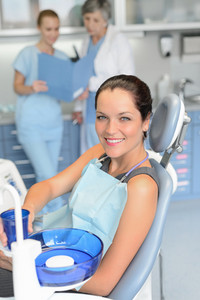 Woman patient sitting chair dental surgery checkup professional dentist team background