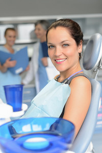 Woman patient sitting chair dental surgery professional dentist team checkup