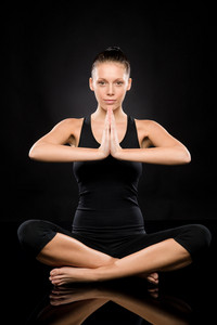 Woman performing yoga sitting on the floor with clasped hands