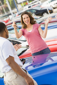 Woman picking up keys to new car from lot