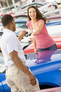Woman picking up keys to new car from salesman