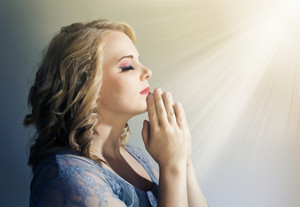 Woman praying with light beams shining down.