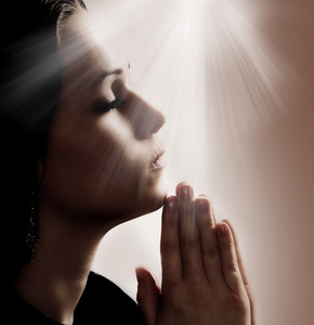 Woman praying with lights shining down