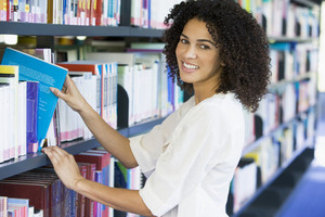 Woman pulling a library book off shelf
