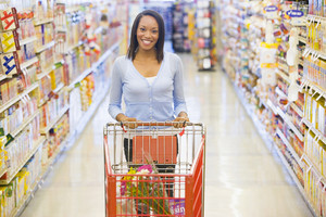 Woman pushing trolley along aisle in supermarket