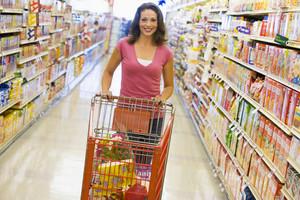 Woman pushing trolley along supermarket grocery aisle