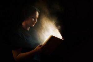 Woman reading an open book with abstract lights and glows.