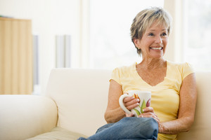 Woman relaxing in living room with coffee smiling