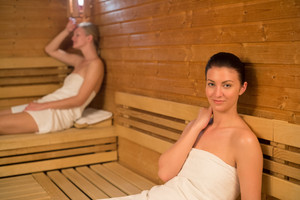 Woman relaxing in sauna with friend in background