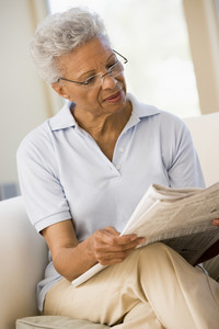 Woman relaxing with a newspaper smiling