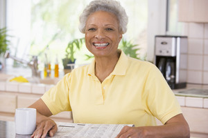 Woman relaxing with newspaper in kitchen and smiling