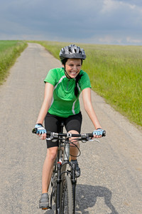 Woman riding bike on cycling path in the countryside meadow