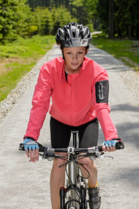 Woman riding mountain bike on sunny countryside cycling path
