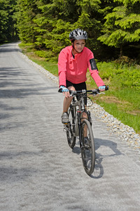 Woman riding mountain bike on sunny cycling path in forest