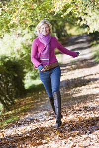 Woman running along autumn path looking to camera