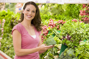 Woman shopping for fresh vegetables in supermarket