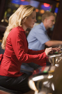 Woman sitting at slot machine in casino parlour