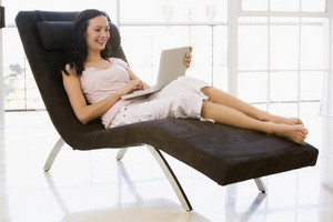 Woman sitting in chair using laptop smiling