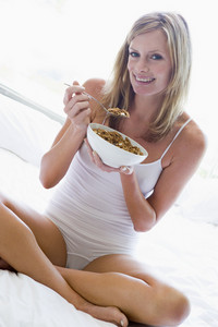 Woman sitting on bed eating cereal smiling