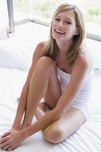 Woman sitting on bed smiling