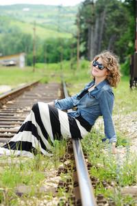 Woman sitting on railway tracks