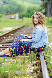 Woman sitting on railway tracks