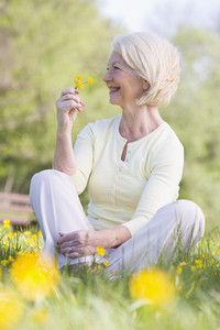 Woman sitting outdoors smiling and holding a Buttercup flower