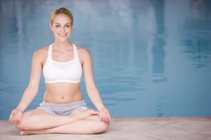 Woman sitting poolside doing yoga smiling