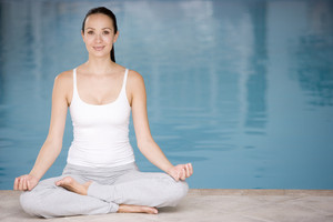 Woman sitting poolside doing yoga