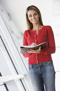Woman standing in corridor with personal organizer smiling