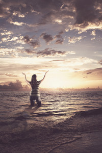 Woman standing in the ocean and lifting her arms up in praise.
