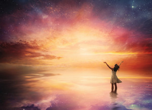 Woman stands in praise before a beautiful night sky.